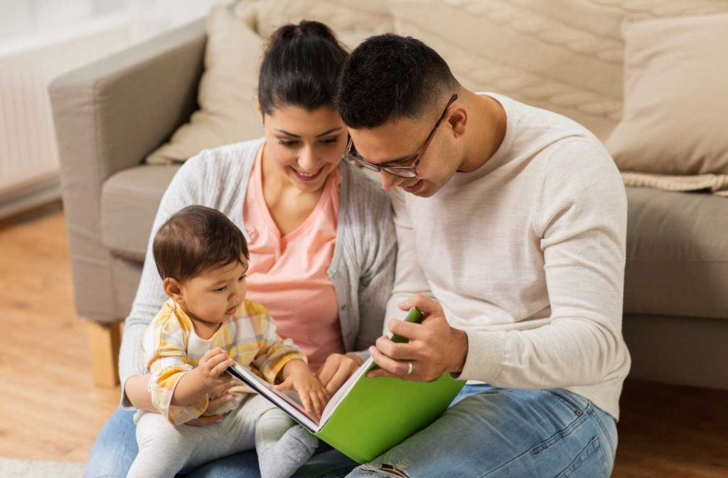 family gathered around book while baby touches pages in the warm lighting of a livingroom