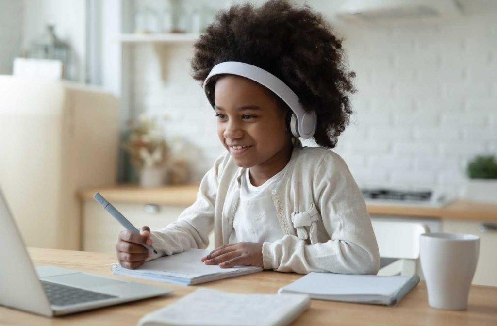 Child in white background and clothing happily learning over computer
