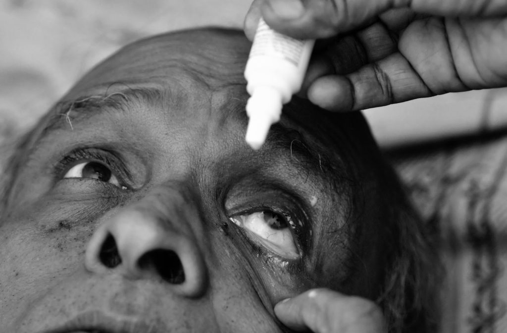 Eyedrops being administered to older man to dilate his eyes
