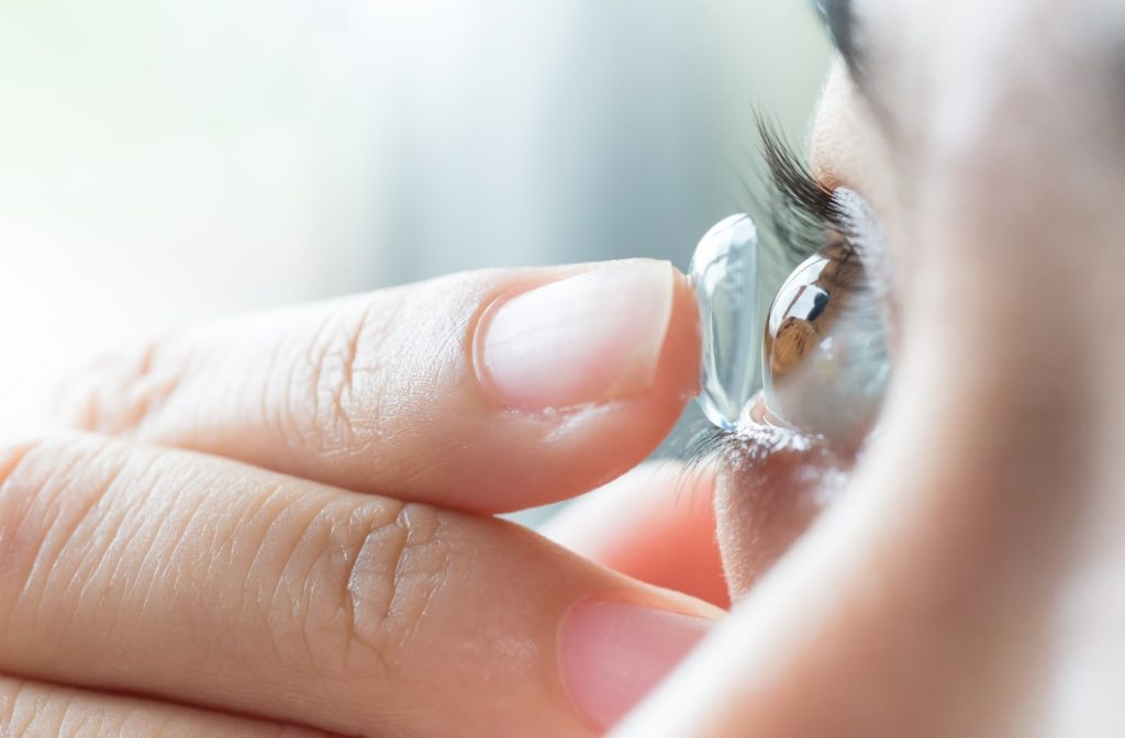 A woman putting in soft contact lenses to help correct her vision due to astigmatism