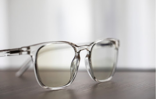 A pair of translucent glasses sitting on a wood surface