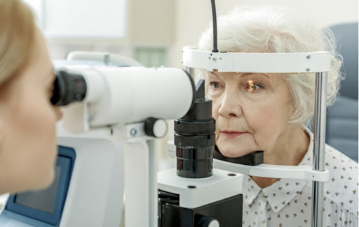 An optometrist giving an elderly woman an eye exam to protect her vision against conditions like glaucoma and tunnel vision